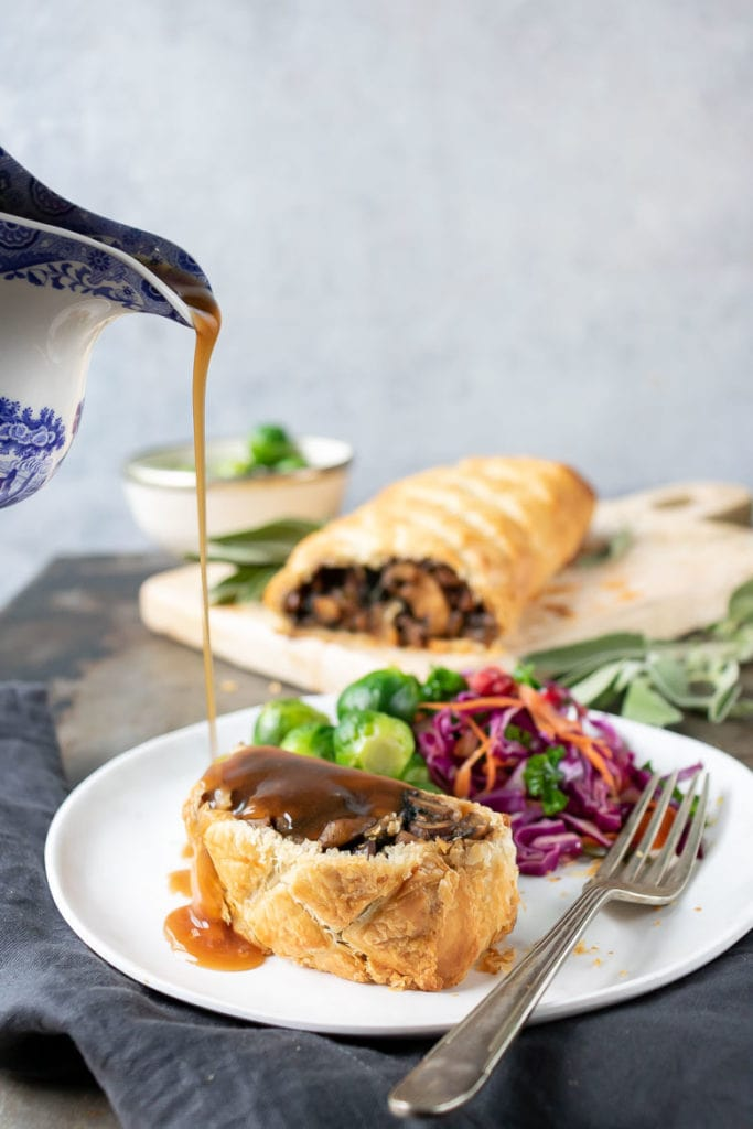 Pouring vegan gravy on a vegetarian wellington made with mushrooms.