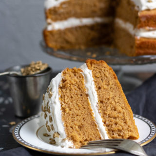 A slice of vegan pumpkin cake with ginger frosting with the layer cake in the background.