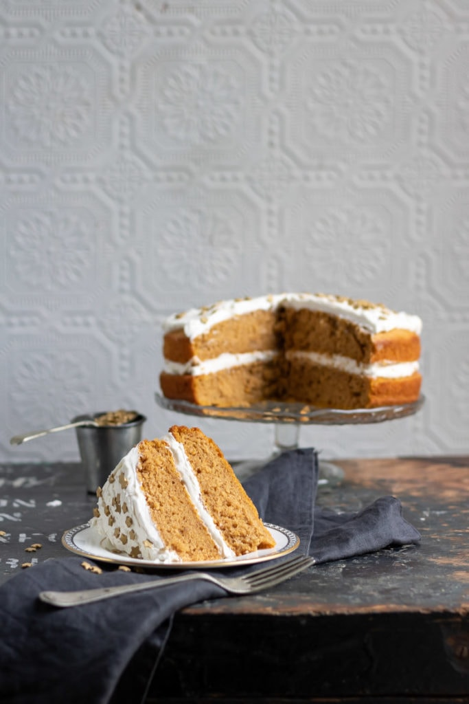 A vegan pumpkin cake recipe with ginger frosting, with a slice cut out on a plate in front.