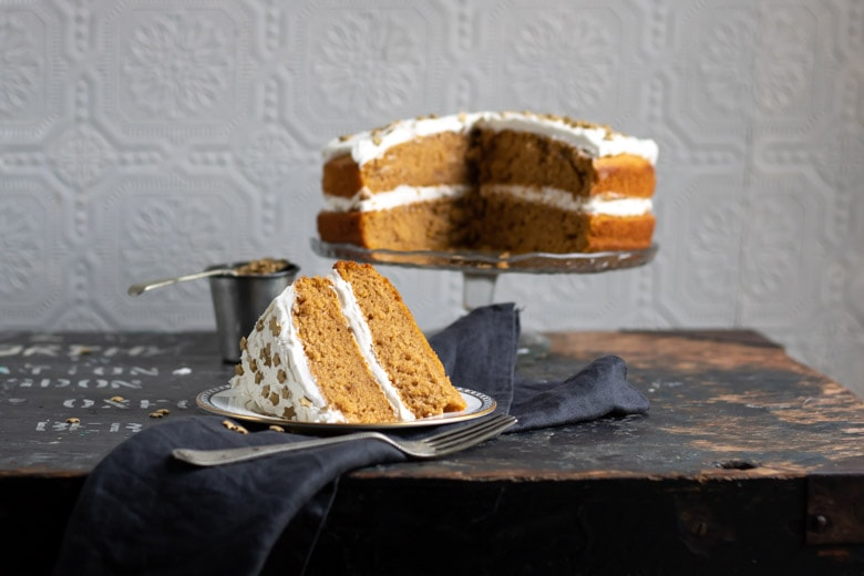 Vegan pumpkin cake recipe with ginger frosting, with a slice out and set in front on a plate.