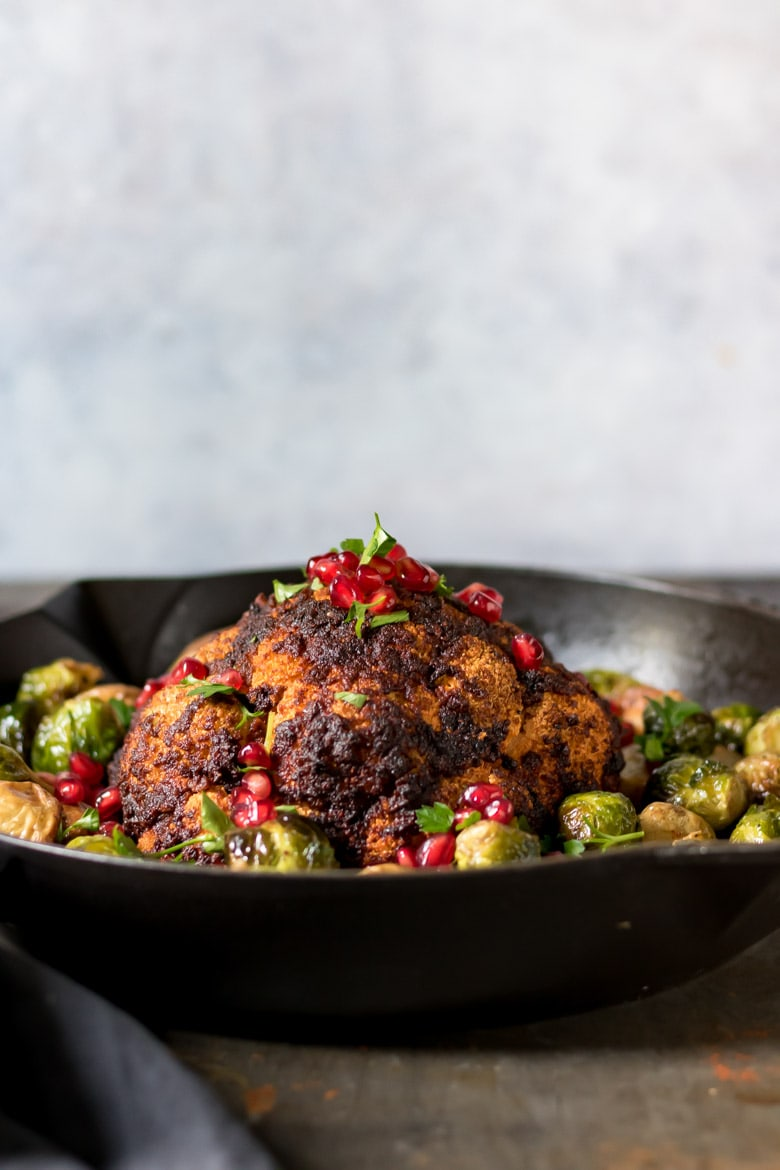 Side view of a pan with a whole cauliflower roasted with brussels sprouts.