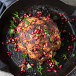 Overhead photo of a whole baked cauliflower in a skillet with pomegrante arils and fresh herbs.