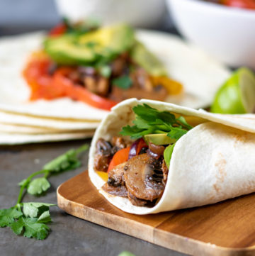 Vegan fajitas with mushrooms and vegetables on a wooden board