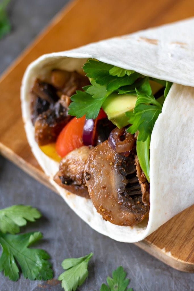 Close up of the fillings of a vegan fajita recipe - mushrooms and peppers in a soft flour tortilla.