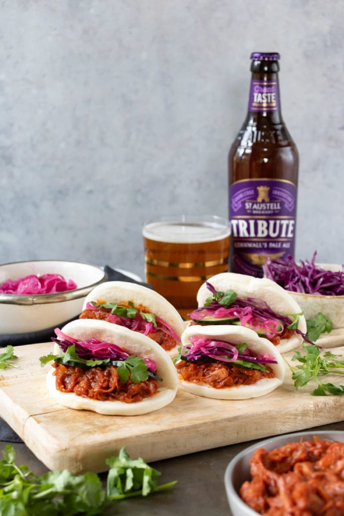 vegan jackfruit bao buns with quick pickled red onions on a board in front of a glass of beer