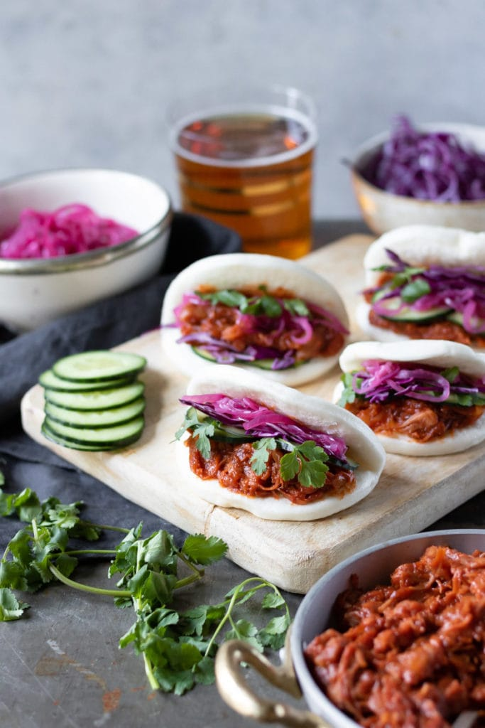 A wooden tray with pulled jackfruit bao buns, with pickled onions on the side