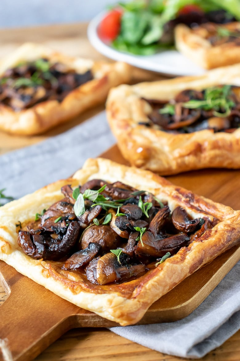 Close up of mushrooms on puff pastry on a wooden board, with sprigs of thyme.