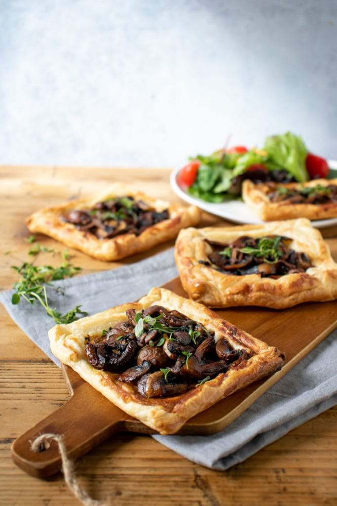 A wooden table with mushroom pastries - a dinner or appetizer.