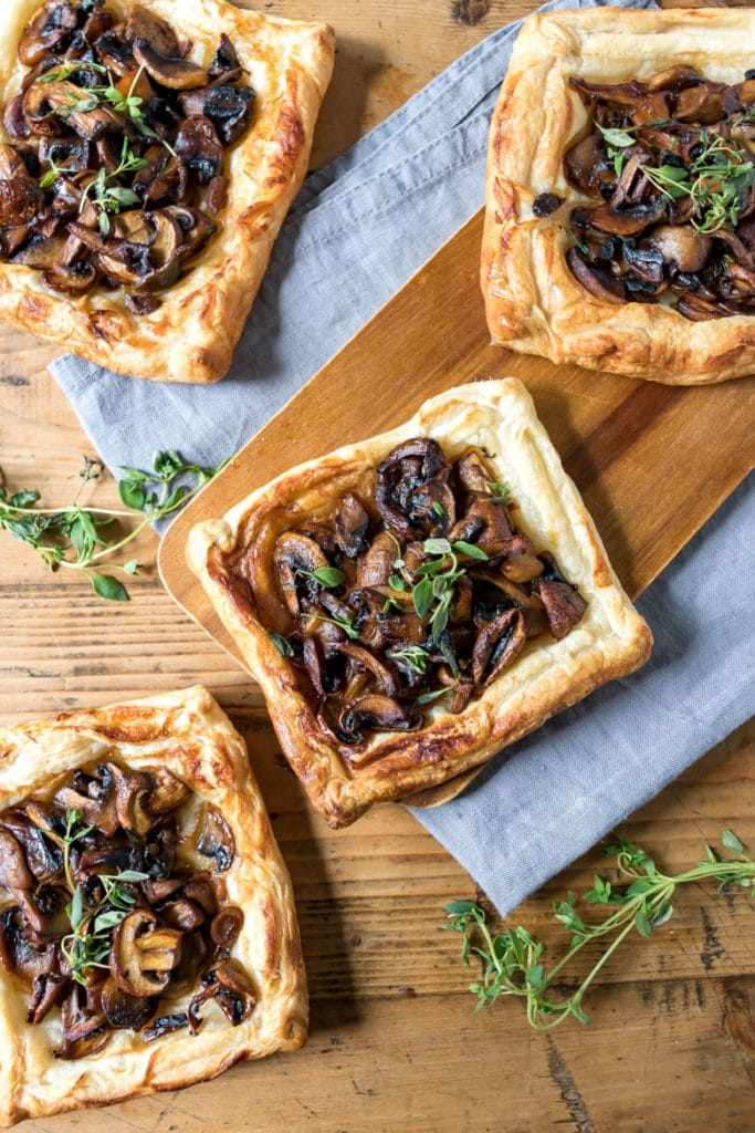 Mushroom tart appetizers made with puff pastry on a wooden table.