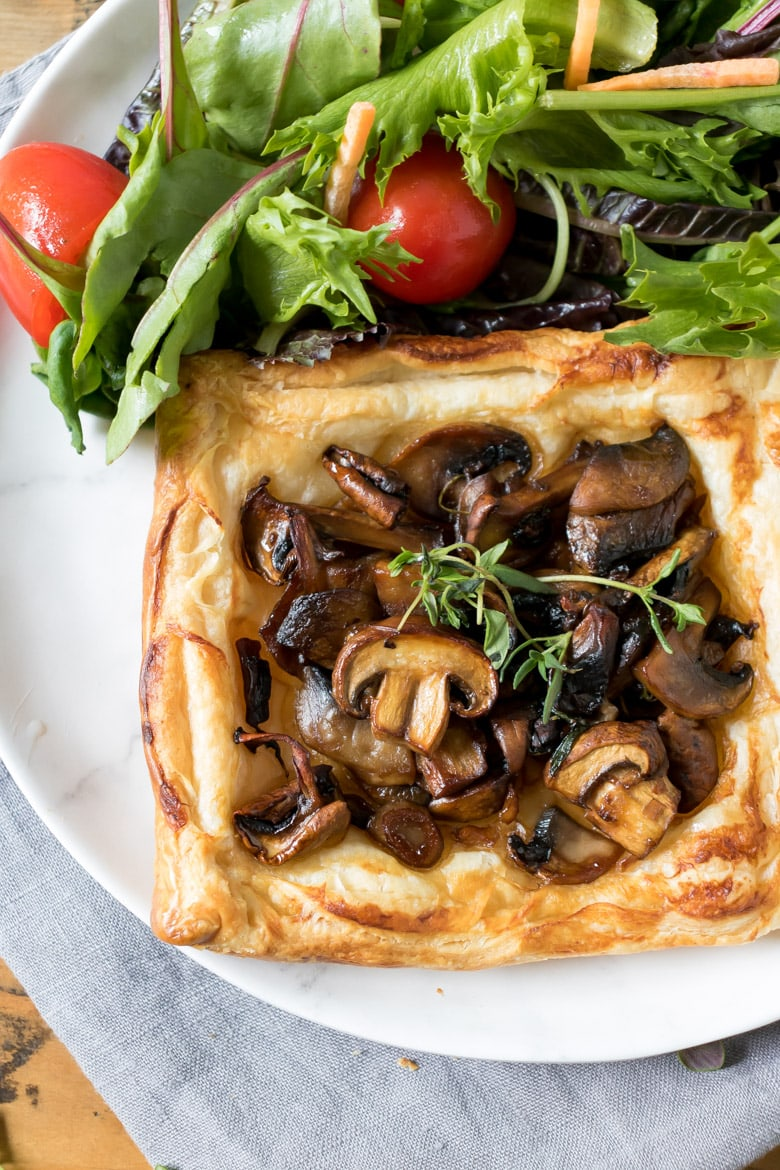 Close up of a puff pastry mushroom tart next to salad on a plate.