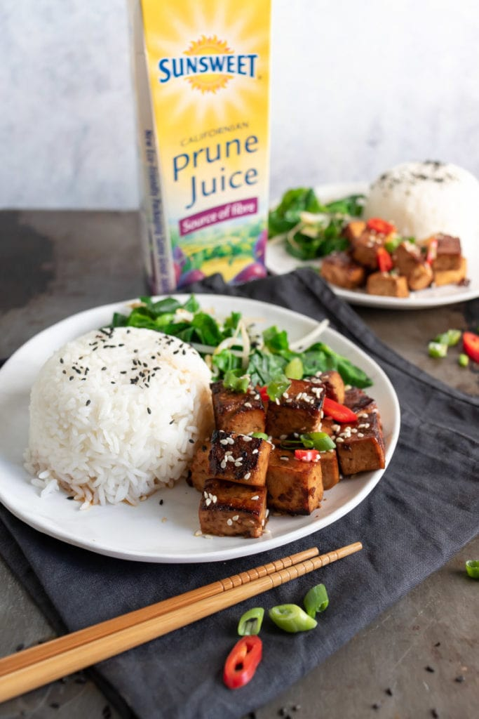 A plate of Asian tofu and rice next to a bottle of prune juice