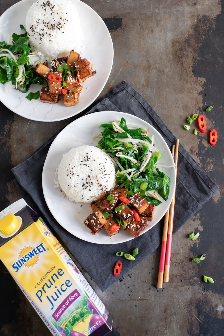 Overhead shot of a table with Asian tofu, greens and rice next to a bottle of Sunsweet Prune Juice.