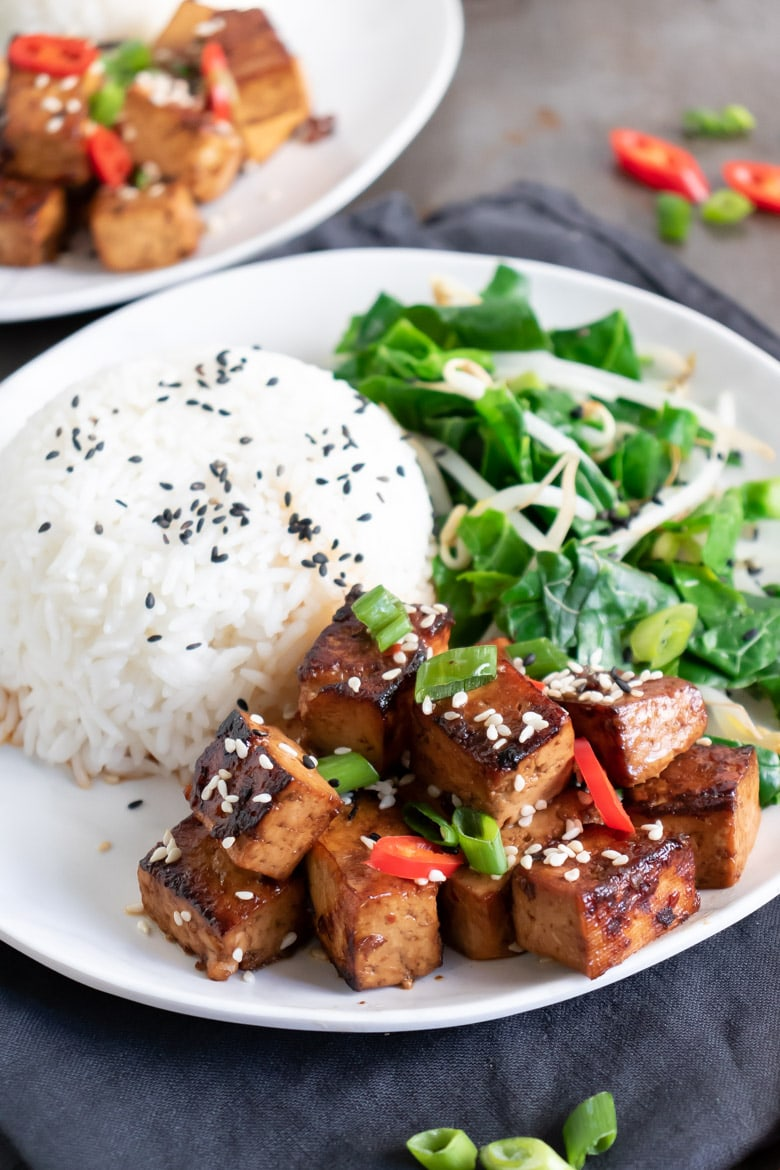 A plate with rice, stir fried greens and Asian tofu with Chinese marinade.
