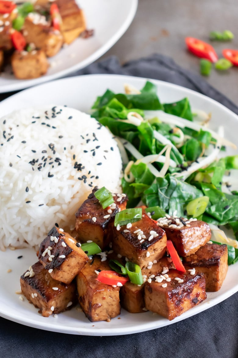 Close up of a plate of Chinese tofu, rice and greens recipe.