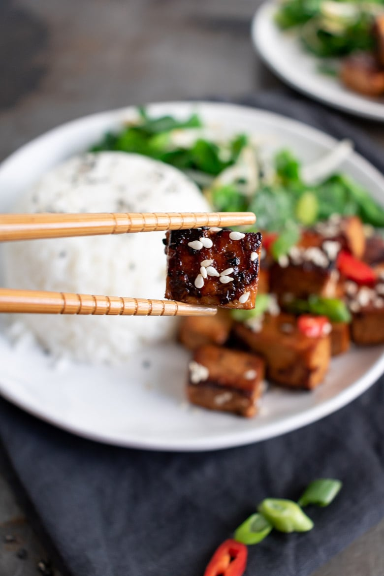 Close up of chopsticks holding a piece of Asian tofu with the plate of food in the background.