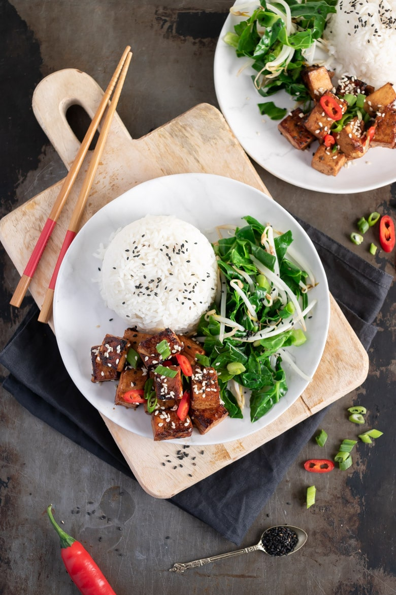 Overhead photo of a plate of Asian tofu and rice on a plate on a wooden board.