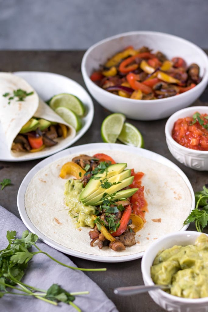 An open vegan fajita with mushrooms, peppers, avocado and salsa.