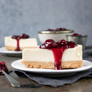 Side view of a slice of dairy free cheesecake. The vegan cashew cheesecake is topped with a quick mixed berry compote.