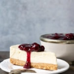 A piece of cashew cheesecake (vegan, dairy free) with a berry topping on a plate in front of a bowl of berry compote.