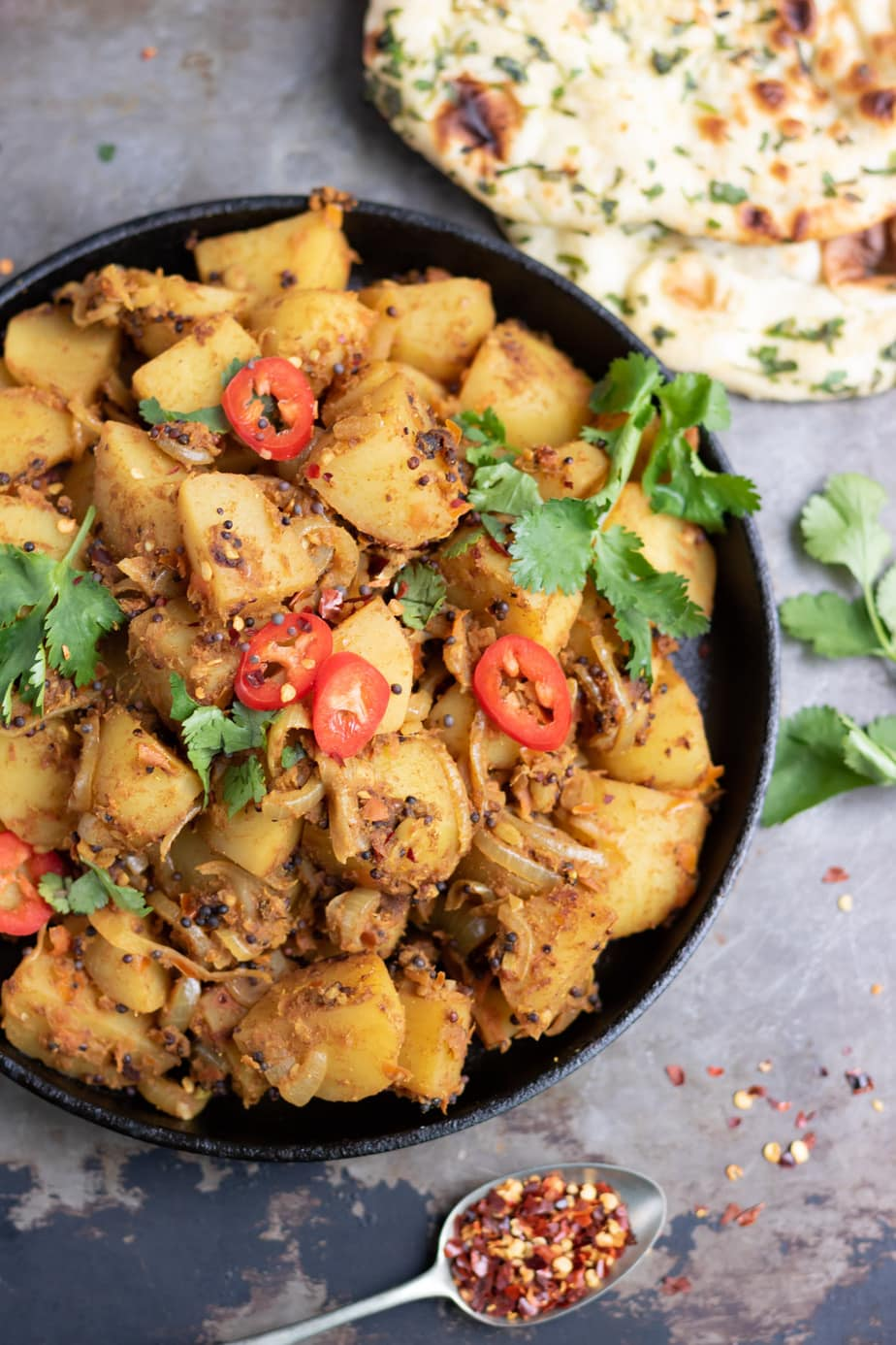 Close up of a dish of Bombay Potatoes with naan and a teaspoon of chilli flakes.