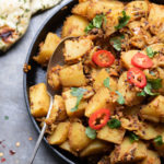 A dish of Bombay Potatoes (aka Bombay aloo Indian potato side dish), with naan and sprinkled with coriander and red chillis.
