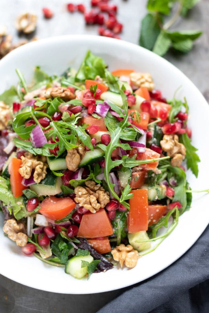 A bowl of Persian salad with walnut pomegrante dressing.