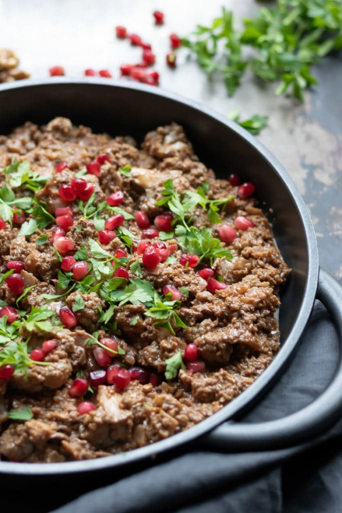 Close up of a cast iron pan of fesenjan (aka fesenjoon) a Persian pomegranate and walnut stew recipe.