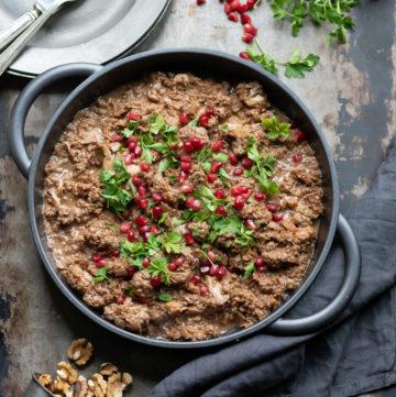 Overhead shot of a dish of Persian fesenjan - a pomegranate walnut stew recipe.