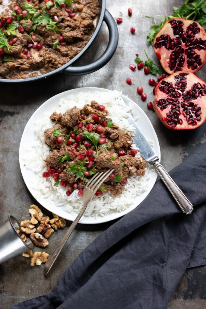 A plate with rice and Persian fesenjan next to walnuts and pomegranates.