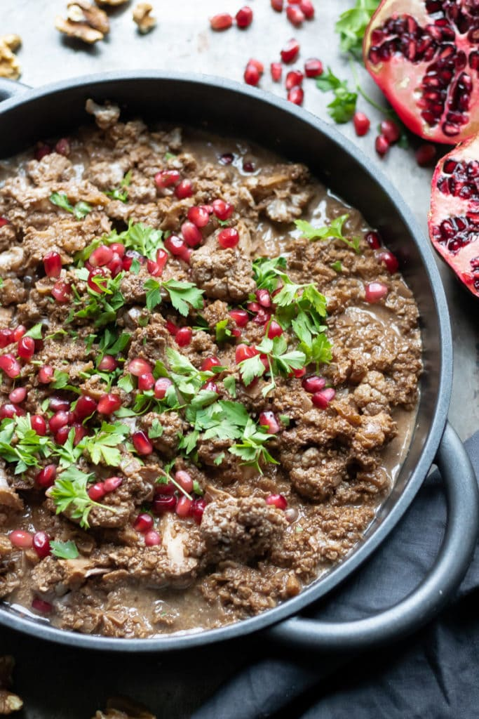 Close up of a serving dish of Koresh Fesenjoon - a Persian walnut stew.