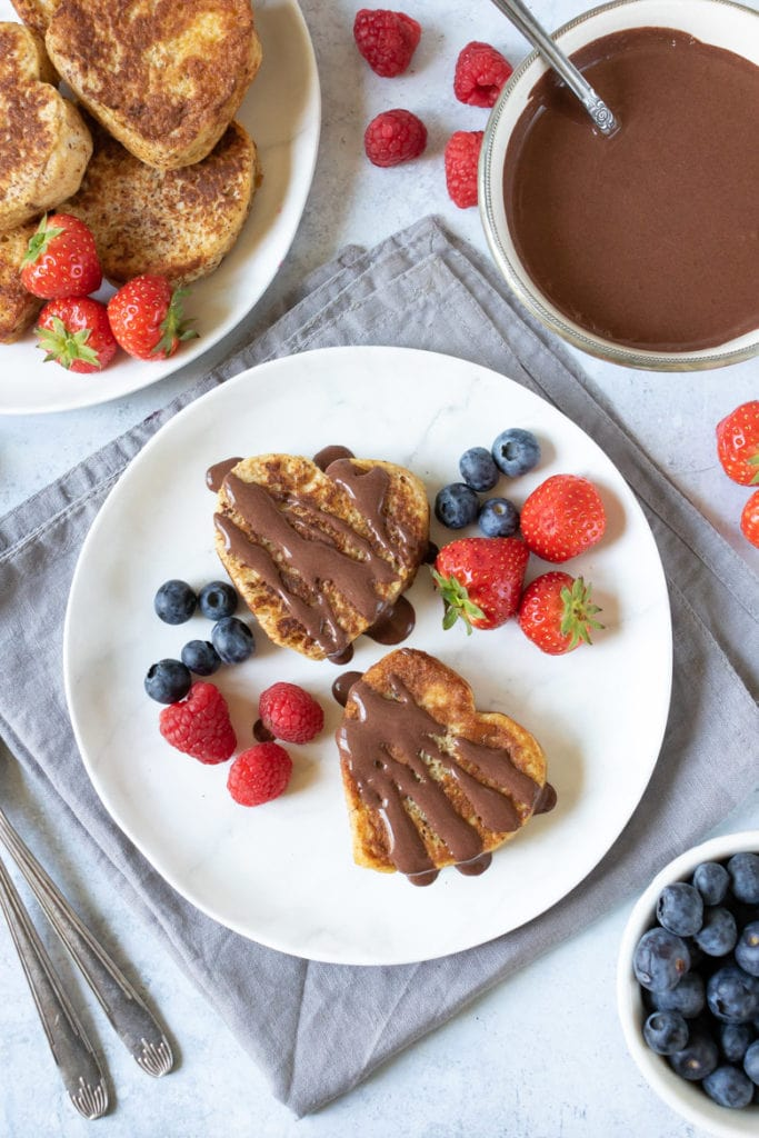 A plate with two heart-shaped cinnamon french toast with chocolate sauce and berries