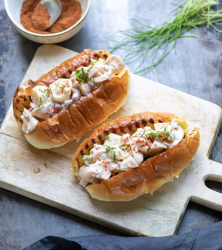 Two vegan lobster rolls on a wooden board