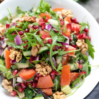 A plate of rocca salad, with rocket arugula, cucumber, tomatoes, red onion, pomegranate and Middle Eastern dressing and walnuts
