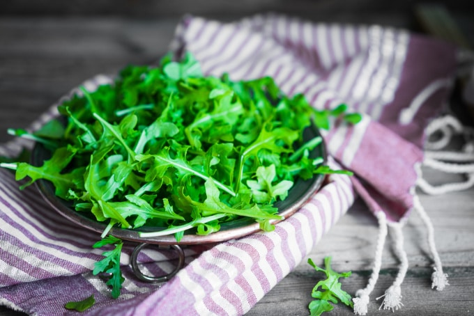 arugula (rocket) on a wooden table with a striped tea towel