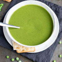 A bowl of thick creamy pea soup next to frozen peas and crackers