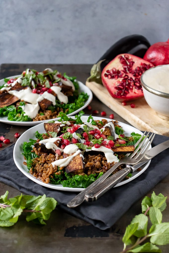 Plates with Persian Salad topped with Baked Aubergines and Tahini Dressing