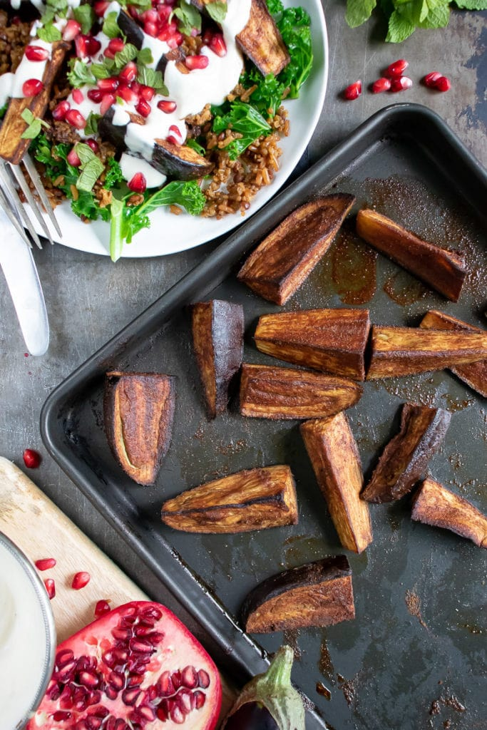 A tray of roasted eggplant wedges next to a persian salad