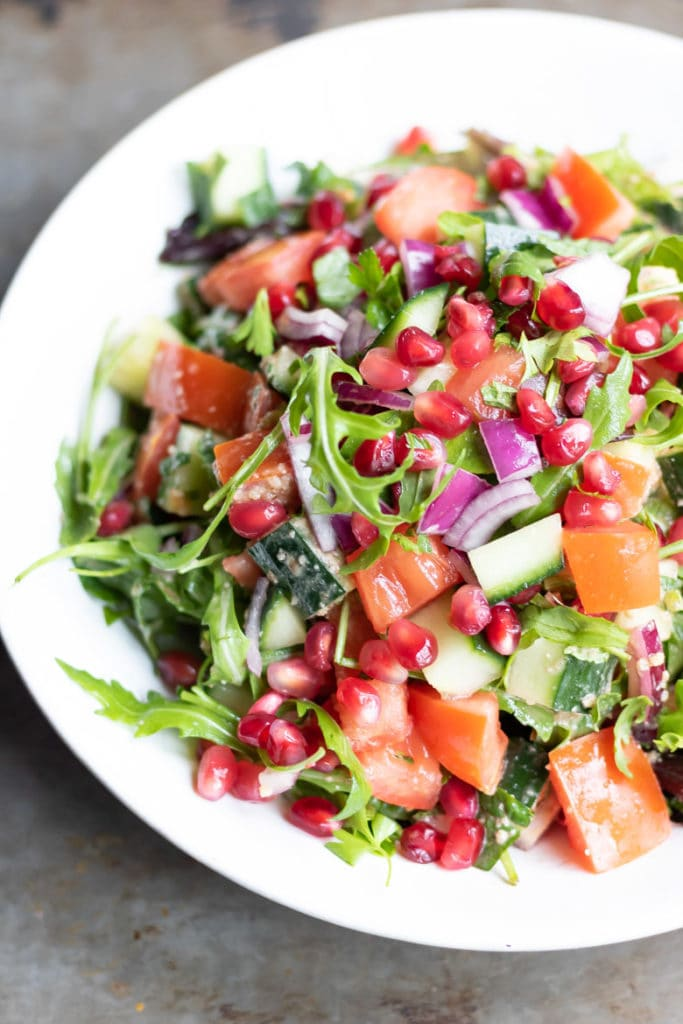 A plate of rocca salad, with rocket arugula, cucumber, tomatoes, red onion, pomegranate and Middle Eastern dressing