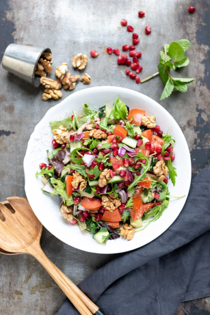 A plate of rocca salad, with rocket arugula, cucumber, tomatoes, red onion, pomegranate and Middle Eastern dressing and walnuts with pomegranate arils and walnuts on the table next to it.
