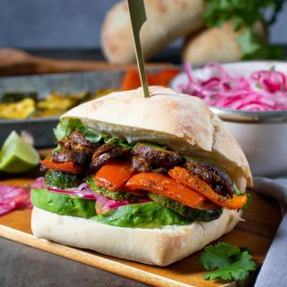 Peruvian sandwich full of spiced vegetables in a roll, with recipe ingredients in the background.
