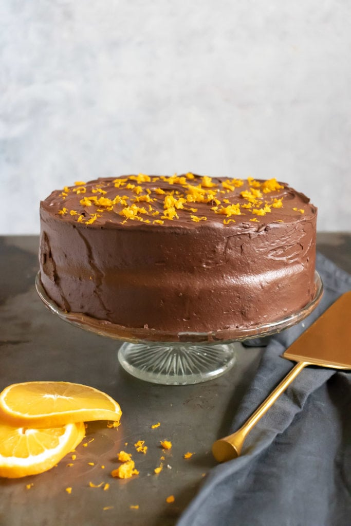 A frosted Chocolate Orange Cake on a glass cake stand.