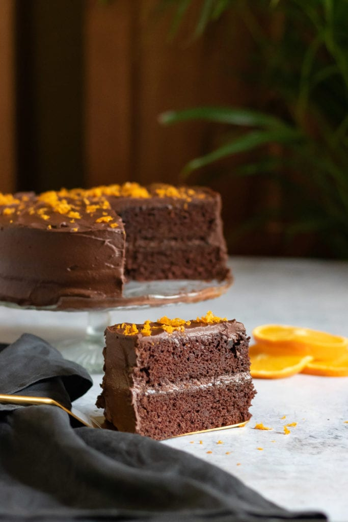 A slice of Chocolate Orange Cake in front of the rest of the easy layer cake, with orange zest on top.