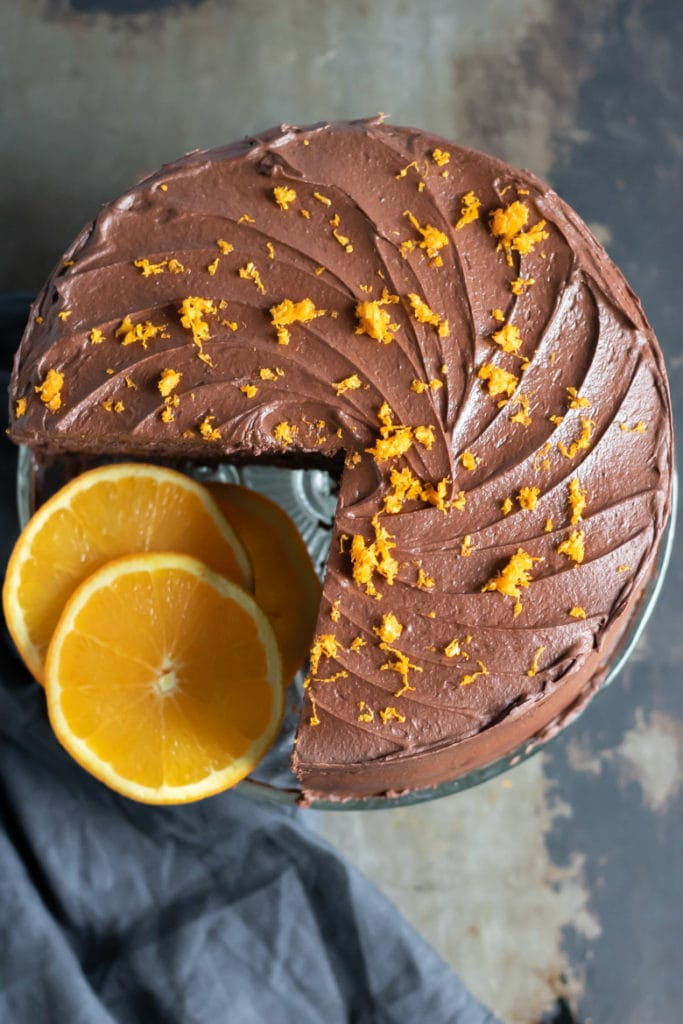 Overhead shot of a chocolate orange cake with orange zest sprinkled on top and a slice missing.
