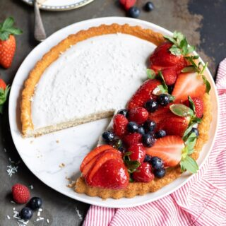 A Coconut Fruit Flan piled with glazed berries with a slice cut out and on a plate behind it.
