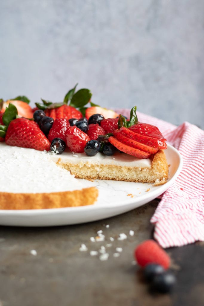 Side view of a Coconut Fruit Flan with a slice cut out. It has a sponge cake crust, creamy filling and is piled with glazed berries.