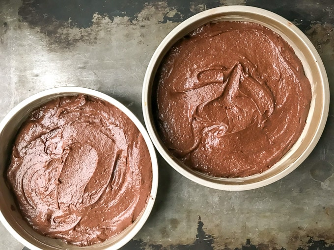 Two round baking pans filled with batter for chocolate orange cake recipe