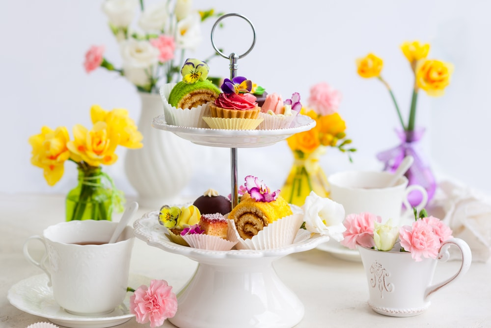 A cake stand full of food for afternoon tea, with tea cups and flowers.