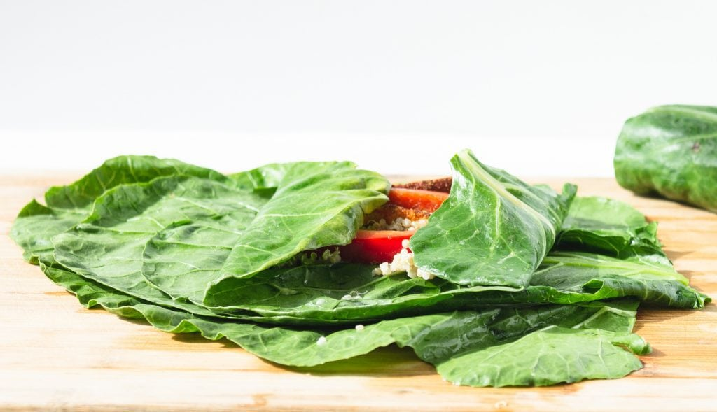 collard leaf with quinoa and red pepper being rolled into a wrap