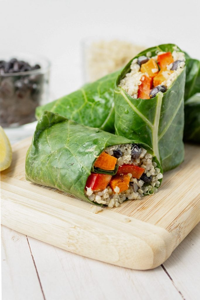 collard wraps with quinoa and sweet potato cut on a wooden board.