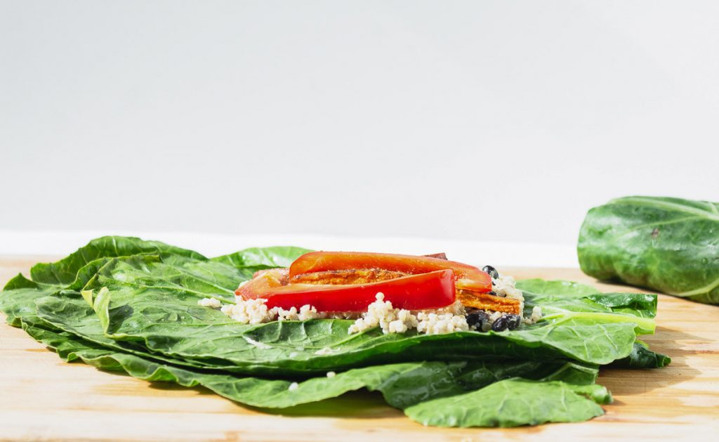 collard leaf with quinoa and peppers on it